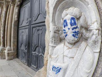 La fachada de Platerías de la catedral de Santiago de Compostela ha aparecido esta mañana con un grafiti en una de sus figuras, que aparece pintada emulando a uno de los miembros de Kiss