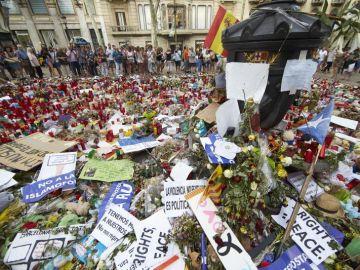 Ciudadanos y turistas observan un homenaje a las víctimas del 17A