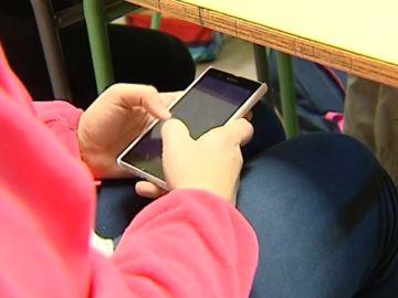 Un alumno usando el móvil en clase