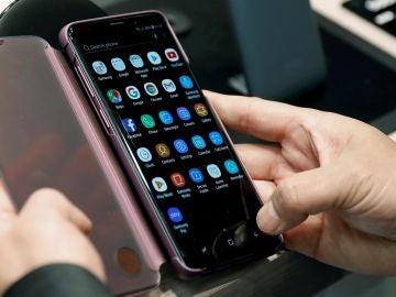 Una persona revisa la pantalla de un móvil