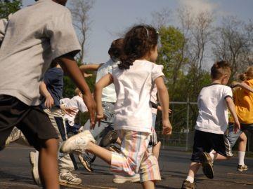 Imagen de archivo de niños corriendo en un colegio.