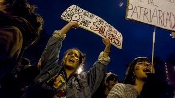 Dos manifestantes sujetan pancartas durante el 8M
