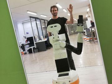 Pablo Lanillos junto a Tiago, un robot de sólo un brazo que, a diferencia de otros humanoides, es capaz de reconocer su propio cuerpo frente a un espejo