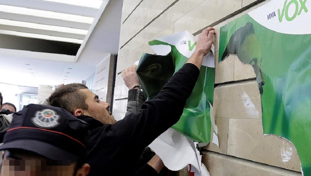 Un grupo de manifestantes quita carteles de Abascal a las puertas de un acto de Vox