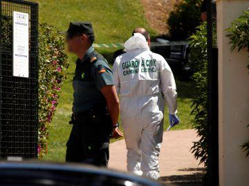 Guardias civiles en la entrada de la vivienda de Ayamonte en la que aparecieron los dos cuerpos
