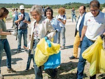 La reina Sofía recogiendo basura en un entorno natural