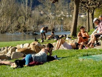 Imagen de archivo de personas tomando el sol en la zona fluvial del río Miño