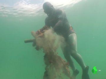 Buzo retirando basura del fondo marino