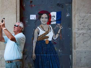 Un señor toma una fotografía junto al grafitti de 'madame Colau'
