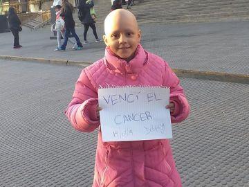 """Delfina sostiene un cartel con el mensaje """"vencí el cáncer"""""""
