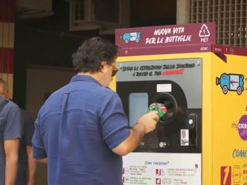 UN hombre tirando una botella de plástico a una máquina en Roma