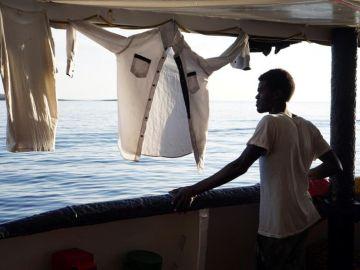 """Un migrante mira desde la cubierta de el buque """"Open Arms"""" las costas de Lampedusa (Italia)"""