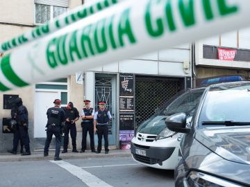 Agentes de la Guardia Civil y Mossos d'Esquadra durante el registro de un domicilio en Sabadell (Barcelona) durante la operación.