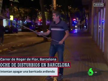 Un vecino intenta apagar el fuego de una barricada con su chándal