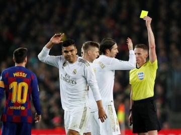 Los jugadores del Real Madrid protestan una amonestación de Hernández Hernández en el Clásico