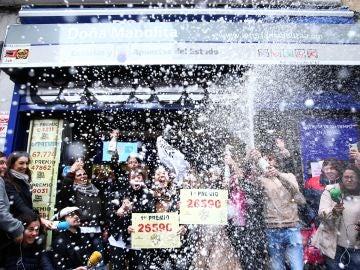 Un grupo de personas celebran en la administración madrileña de Doña Manolita