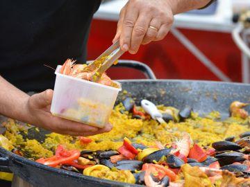 Imagen de una persona cocinando una paella