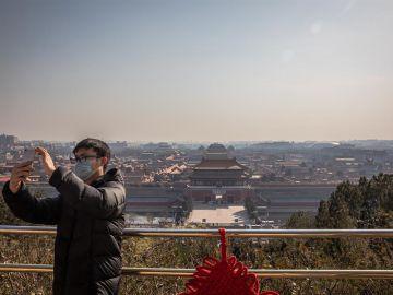 Un hombre se fotografía ante una vacía Ciudad Prohibida de Pekín