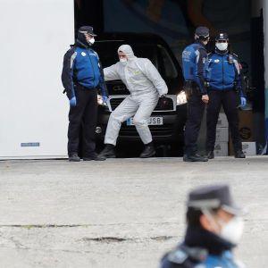 Miembros de la Policía junto a uno de los trabajadores de la morgue en el Palacio de Hielo