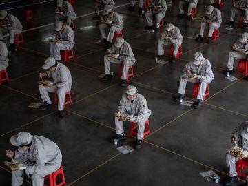 Trabajadores en una fábrica de Wuhan almuerzan guardando la distancia de seguridad por el coronavirus