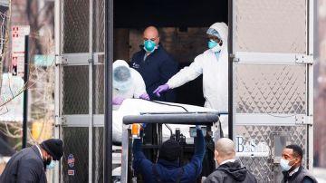Foto de archivo de empleados trasladando un cuerpo a un camión empleado como morgue móvil
