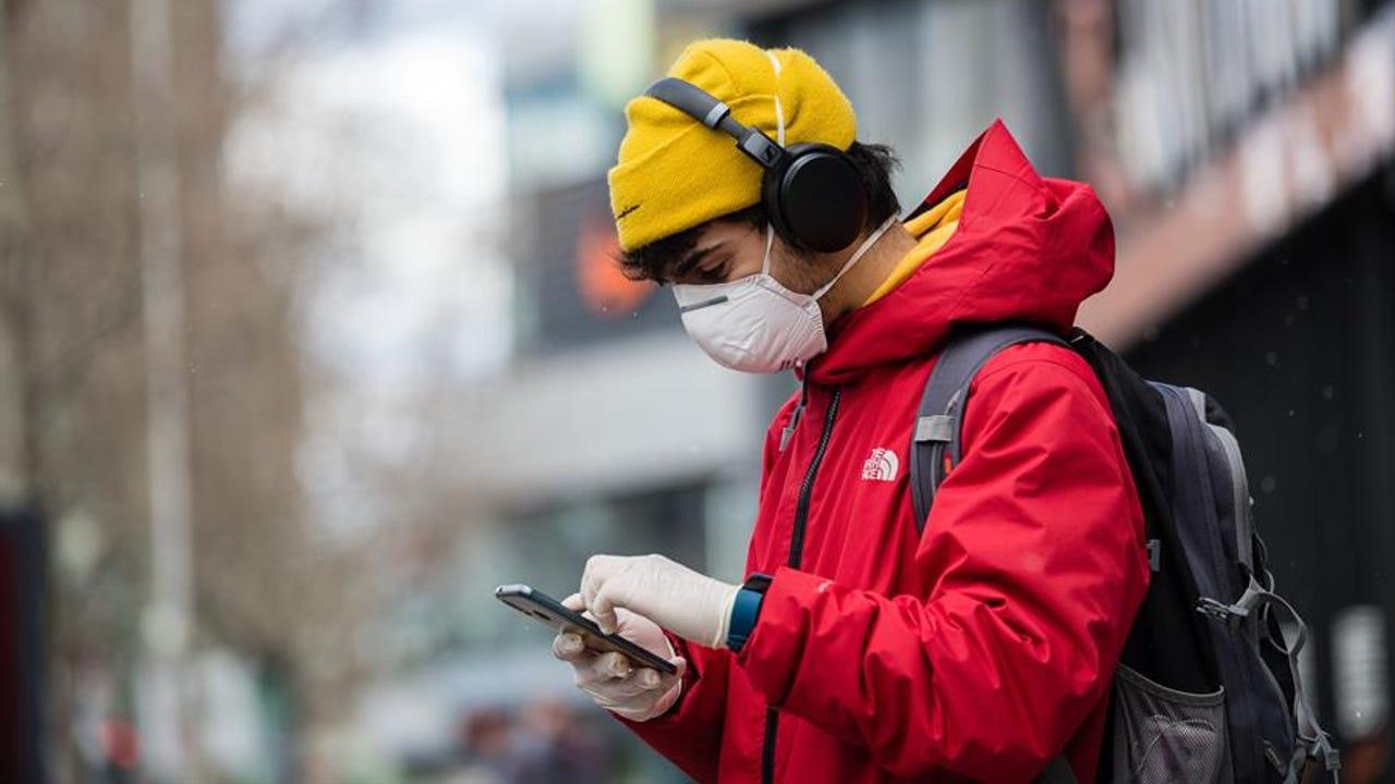 Un joven con mascarilla consulta su móvil