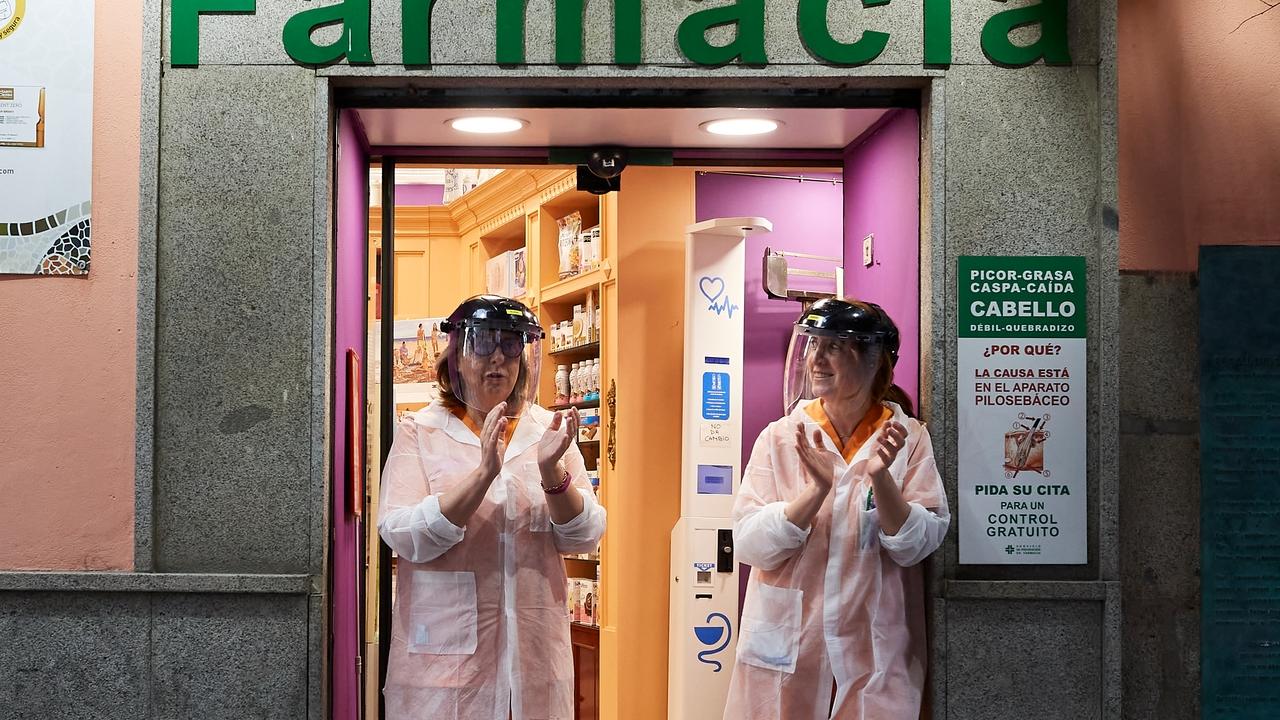 Dos farmacéuticas aplauden a la puerta de su farmacia