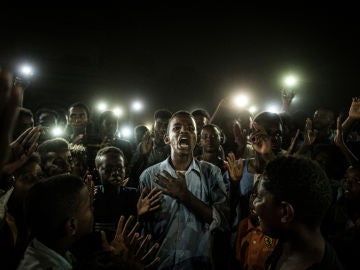 Un joven, iluminado por teléfonos móviles, recita poesía de protesta mientras los manifestantes cantan eslóganes que llaman a un gobierno civil, durante un apagón en Jartum, Sudán