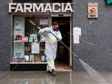Un trabajador delimpieza desinfecta los alrededores de una Farmacia.