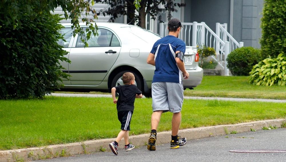 Un niño corre junto a su padre por la calle