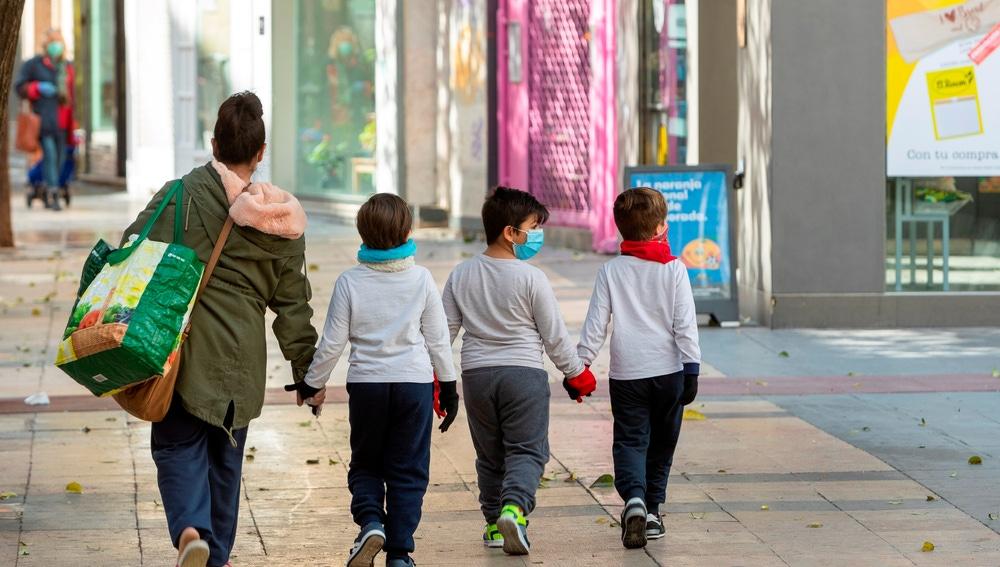 Tres niños acompañan a su madre a hacer la compra en Zaragoza