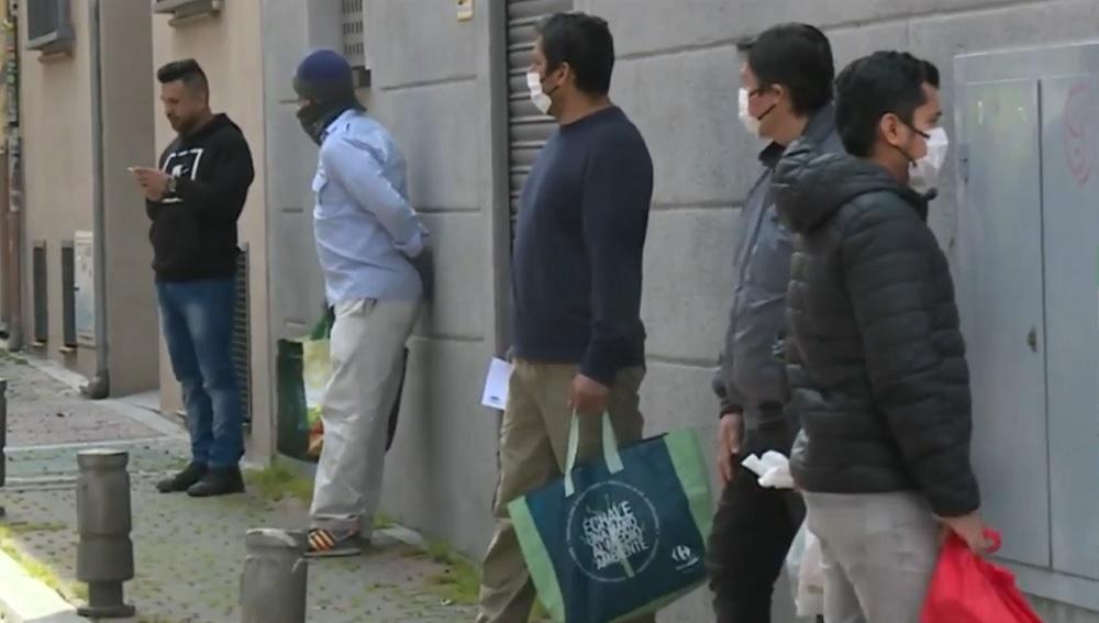 Imagen de personas esperando para recibir alimentos