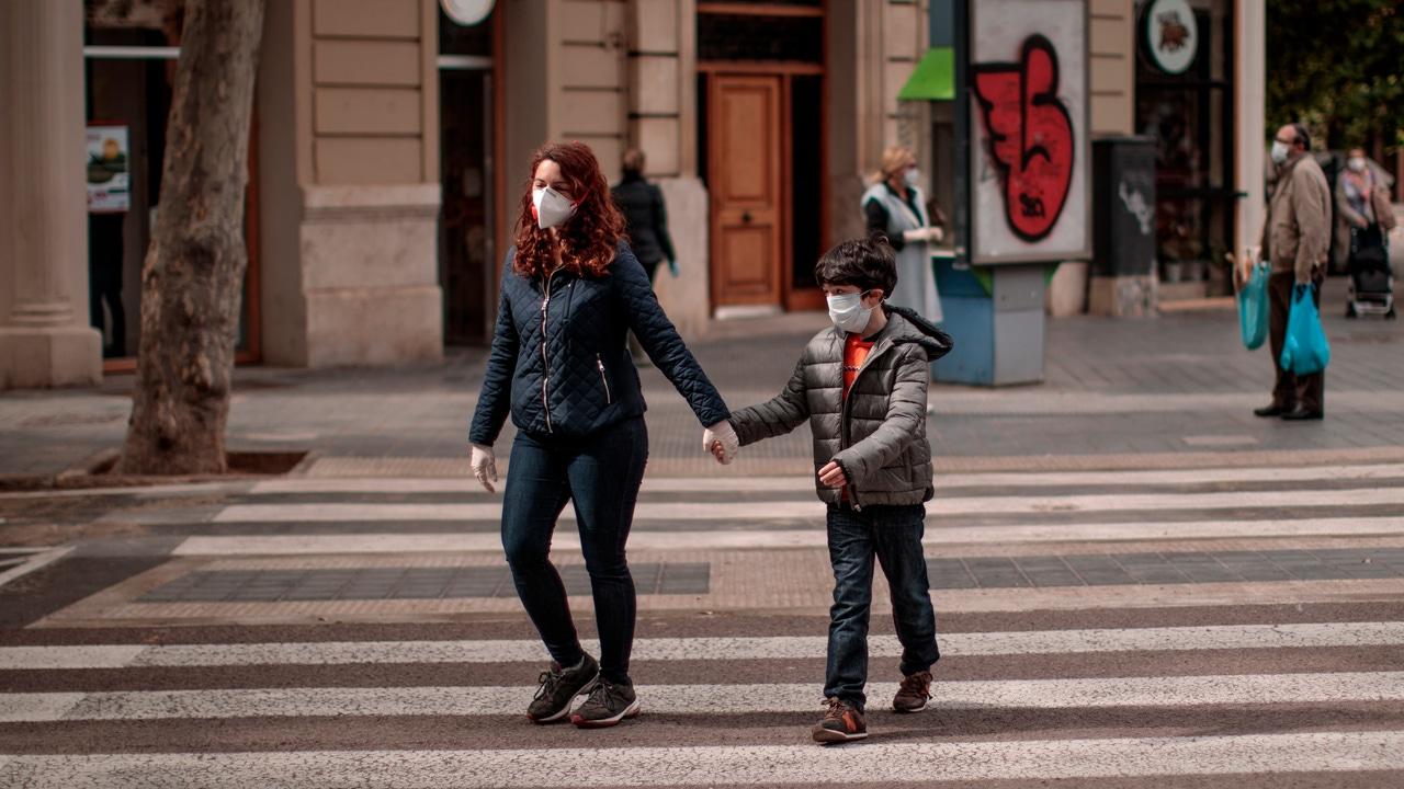 Una mujer acompañada de un niño cruza una calle en Valencia