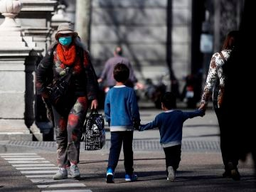 Imagen de una persona adulta paseando con dos menores