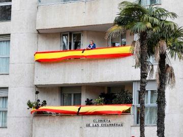 Edificio de la Glorieta de las Cigarreras, en Sevilla, repleto de banderas de España con crespones negros