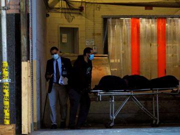Un cuerpo es transportado a un vehículo funerario en el Hospital Mount Sinai West