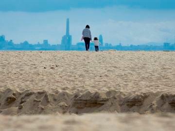 Padres e hijos juegan y pasean en la playa de El Masnou, Barcelona