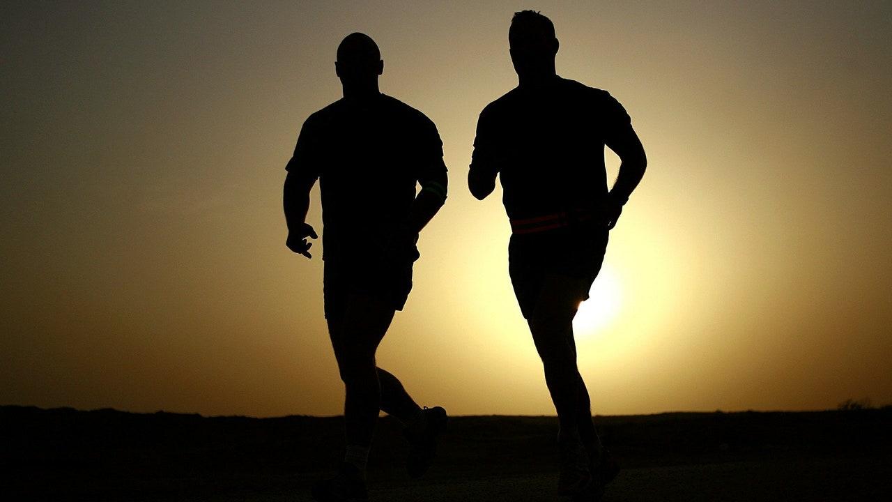 Imagen de dos personas corriendo al atardecer