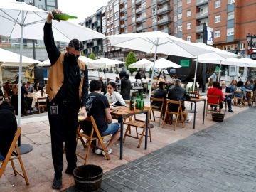 Un camarero escancia sidra en una terraza de Asturias