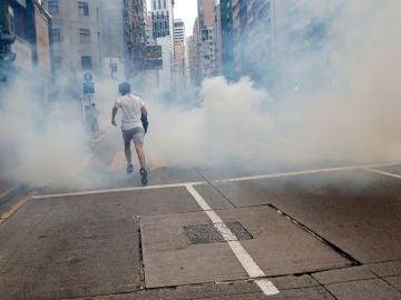 Un hombre huye del lanzamiento de gases lacrimógenos por parte de la Policía en Hong Kong