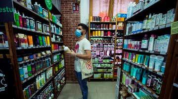 Un hombre frente a una estantería de productos cosméticos.