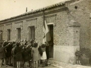 Niños cantando el 'Cara al sol'; otro se oculta tras la pared