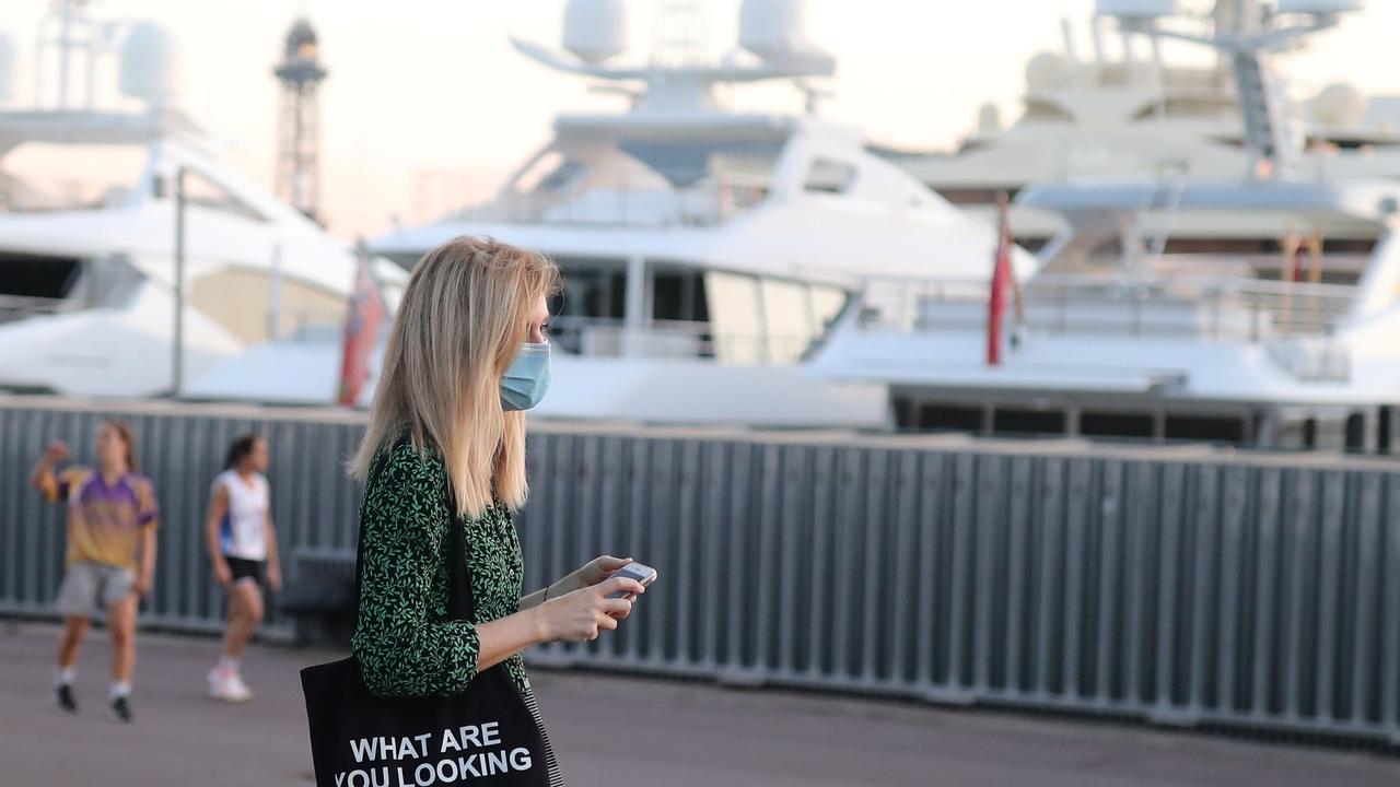 Una mujer camina por Barcelona con la mascarilla