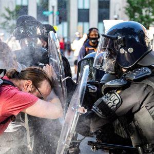 Los agentes rocían pimienta a un manifestante mientras lo empujan hacia atrás