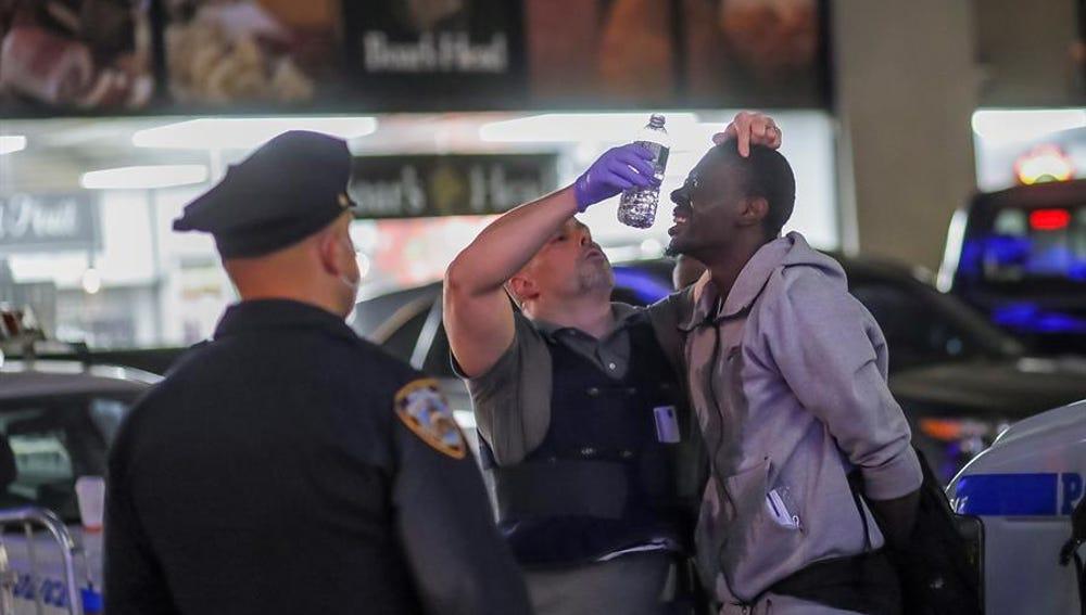 Oficiales del Departamento de Policía de Nueva York prestan ayuda a un detenido