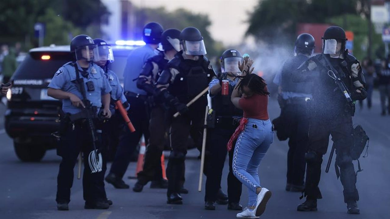 Una agente de Policía rocía con gas pimienta a una manifestante en Minneapolis