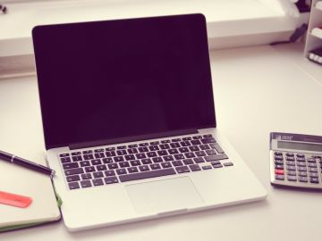 Imagen de archivo de una mesa de escritorio con un ordenador y una calculadora