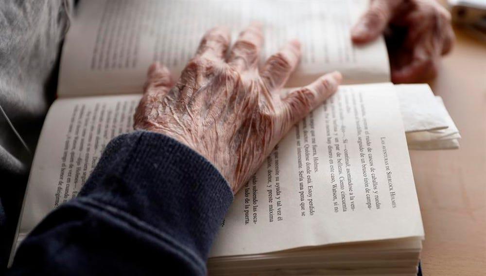 Un anciano lee un libro en una residencia de Madrid
