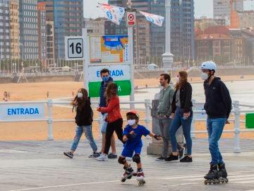 Un grupo de personas pasean por el paseo marítimo de la playa de San Lorenzo de Gijón .