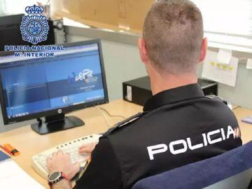 Imagen de archivo de un policía frente a un ordenador